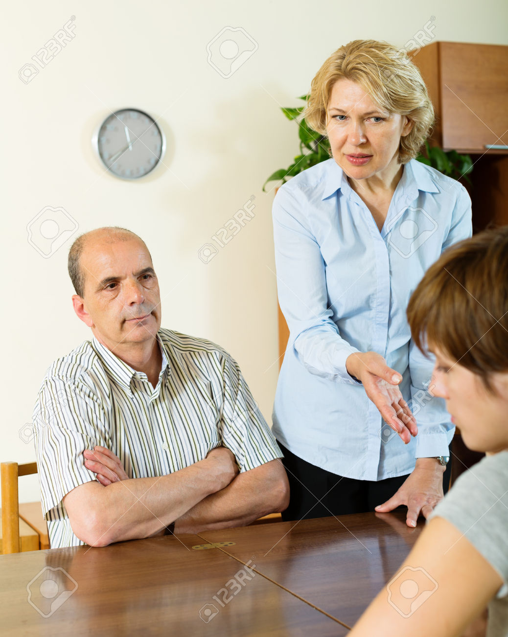 50872864-daughter-and-mature-parents-having-serious-talking-in-home-interior-Stock-Photo.jpg
